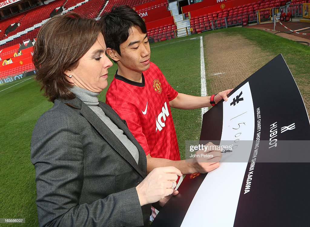 Shinji Kagawa of Manchester United is presented with a cheque for 3,000,000 Japanese Yen by Valerie Servageon Grande of Hublot watches after taking part in a charity shooting event at Old Trafford on March 12, 2013 in Manchester, England.