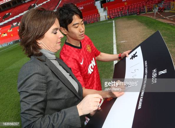 Shinji Kagawa of Manchester United is presented with a cheque for 3000 Japanese Yen by Valerie Servageon Grande of Hublot watches after taking part...