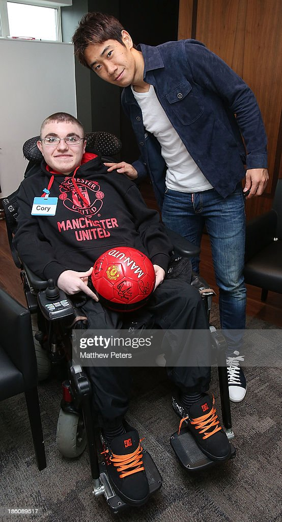 Shinji Kagawa of Manchester United meets Cory August at a Manchester United Foundation Dream Day, for fans with life-limiting illnesses, at Aon Training Complex on October 28, 2013 in Manchester, England.