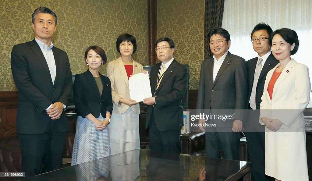 Shinji Mukoono (C), secretary-general of the House of Representatives, receives a draft bill from opposition lawmakers at the Diet building in Tokyo on May 27, 2016. The bill is designed to eliminate discrimination against LGBT minorities.