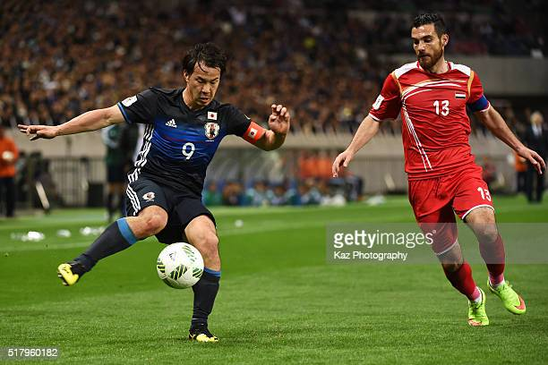 Shinji Okazaki of Japan and Nadim Sabag of Syria compete for the ball during the FIFA World Cup Russia Asian Qualifier second round match between...