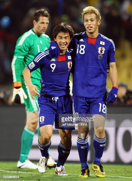 Shinji Okazaki of Japan celebrates scoring with teammate Keisuke Honda during the 2010 FIFA World Cup South Africa Group E match between Denmark and...