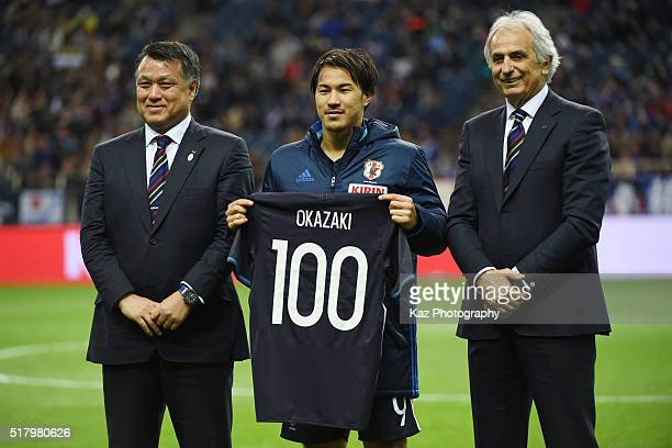 Shinji Okazaki of Japan holds a shirt to mark his 100th appearance for the national team with head coach Vahid Halilhodzic and Japan Football...