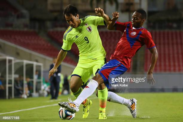 Shinji Okazaki of Japan is tackled by Junior Diaz of Costa Rica during the International Friendly Match between Japan and Costa Rica at Raymond James...