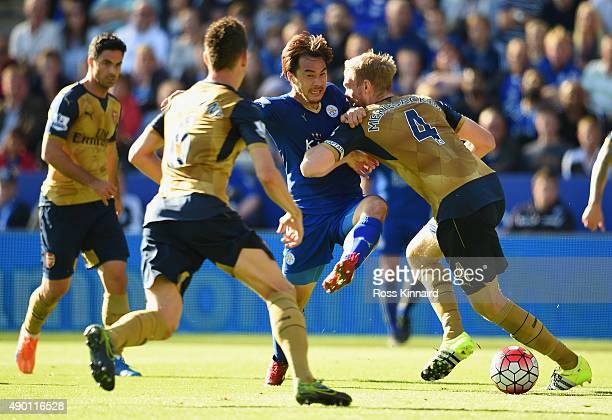 Shinji Okazaki of Leicester City and Per Mertesacker of Arsenal compete for the ball during the Barclays Premier League match between Leicester City...