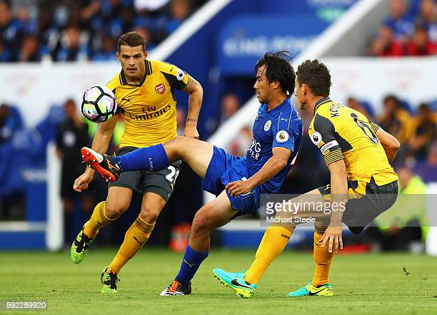 Shinji Okazaki of Leicester City controls the ball while Granit Xhaka of Arsenal and Laurent Koscielny of Arsenal watch during the Premier League...