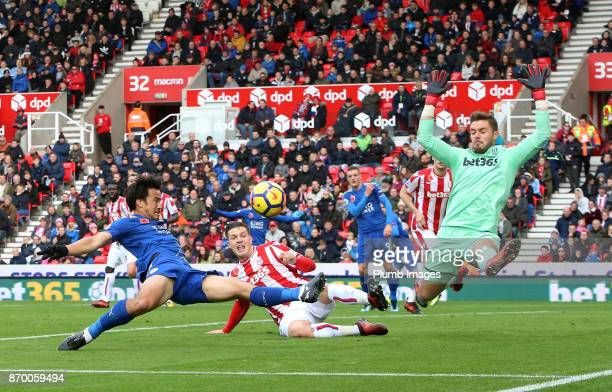 Shinji Okazaki of Leicester City in action with Jack Butland of Stoke City during the Premier League match between Stoke City and Leicester City at...