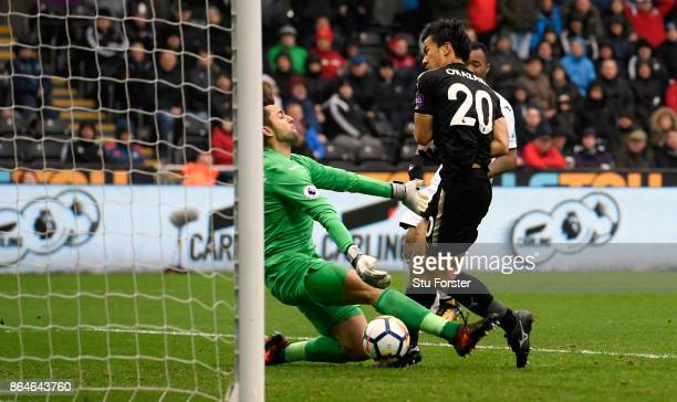 Shinji Okazaki of Leicester City scores the 2nd Leicester goal past Swansea goalkeeper Lucasz Fabianski during the Premier League match between...