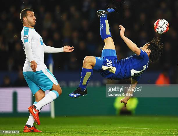 Shinji Okazaki of Leicester City scores their first goal with an overhead kick as Steven Taylor of Newcastle United looks on during the Barclays...