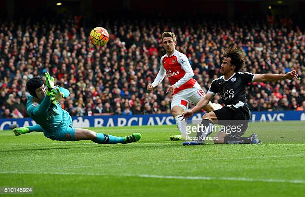 Shinji Okazaki of Leicester City shoots over under pressure from Nacho Monreal of Arsenal as Petr Cech of Arsenal dives during the Barclays Premier...
