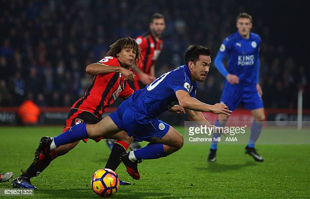 Shinji Okazaki of Leicester City trips over Nathan Ake of Bournemouth during the Premier League match between AFC Bournemouth and Leicester City at...