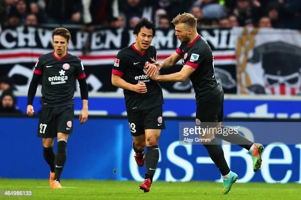 Shinji Okazaki of Mainz celebrates his team's first goal with team mates Nicolai Mueller and Johannes Geis during the Bundesliga match between VfB...