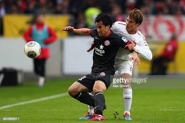 Shinji Okazaki of Mainz is challenged by Gotoku Sakai of Stuttgart during the Bundesliga match between VfB Stuttgart and 1 FSV Mainz 05 at...