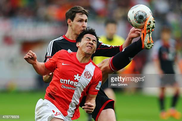 Shinji Okazaki of Mainz is challenged by Philipp Wollscheid of Leverkusen during the Bundesliga match between Bayer 04 Leverkusen and 1 FSV Mainz 05...