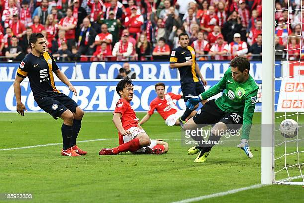Shinji Okazaki of Mainz scores his team's second goal against goalkeeper Faniel Davari of Braunschweig during the Bundesliga match between 1 FSV...