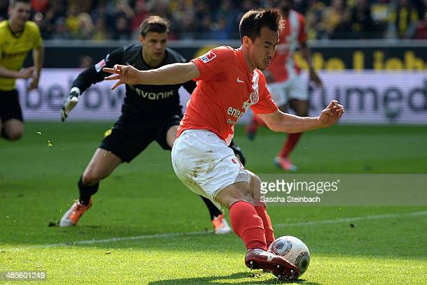 Shinji Okazaki of Mainz scores his team's second goal as goalkeeper Mitchell Langerak of Dortmund looks on during the Bundesliga match between...