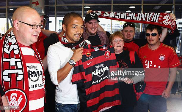 Shinji Ono holds a Western Sydney Wanderers playing shirt as he poses with supporters after his arrival at Sydney International Airport on October 1...