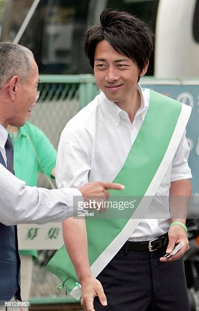 Shinjiro Koizumi son of former Prime Minister Junichiro Koizumi talks with a possible constituent at East Japan Railways Co Yokosuka Station on July...