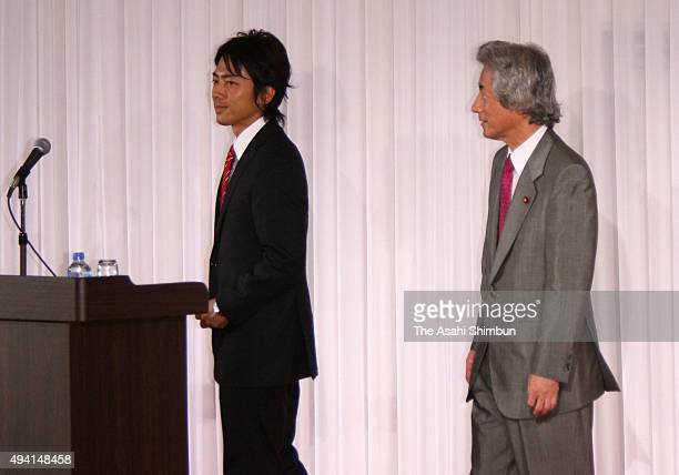 Shinjiro Koizumi walks to address while former Prime Minister Junichiro Koizumi watches his son during an introduction meeting with his supporters on...