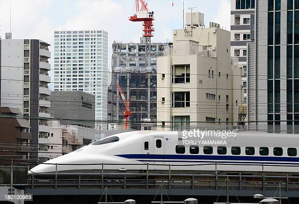 A 'shinkansen' or bullet train speeds amongst buildings in Tokyo on September 9 2013 Japan's economy grew more than initially thought in the June...