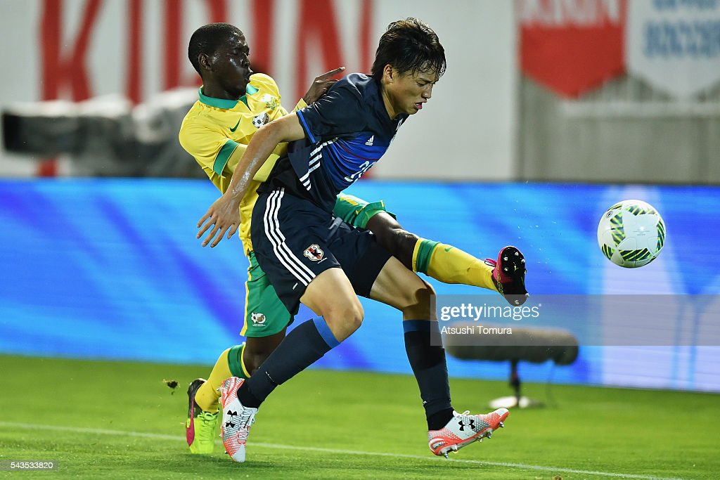 Shinnosuke Nakatani of Japan controls the ball under pressure of Maphosa Modiba of South Africa during the U-23 international friendly match between Japan and South Africa at the Matsumotodaira Football Stadium on June 29, 2016 in Matsumoto, Nagano, Japan.