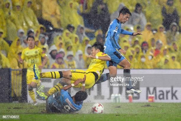 Shinnosuke Nakatani of Kashiwa Reysol is challenged by Takayuki Morimoto and Kei Chinen of Kawasaki Frontale during the JLeague J1 match between...