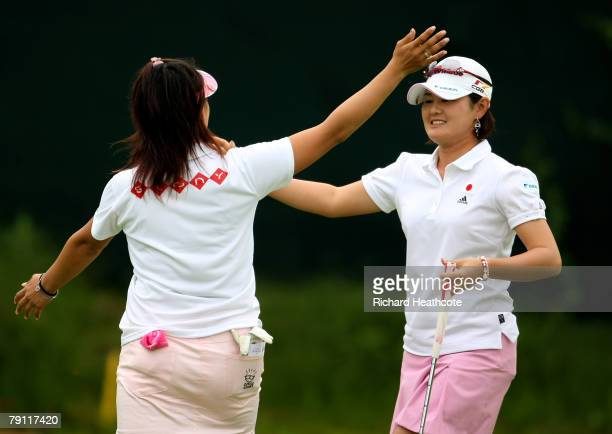 Shinobu Moromizato and Miki Saiki of Japan celebrate a birdie putt on the 18th green during the second round of the Women's World Cup of Golf at The...