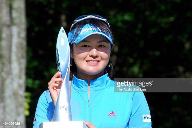 Shinobu Moromizato of Japan poses for photographs with the trophy after winning the AXA Ladies at Tomakomai Golf Resort on August 10 2008 in...