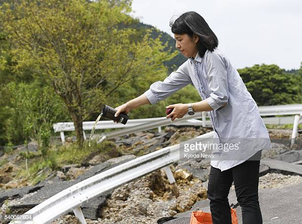 Shinobu Yamato whose son Hikaru has been missing since a major earthquake on April 16 pours tea on June 11 into an area where the son is believed to...