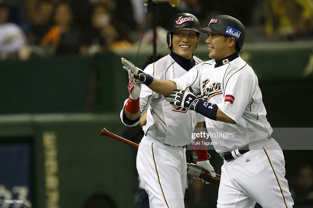 Shinosuke Abe celebrates with Yoshio Itoi after hitting a home run in the second inning during Pool 1 Game 6 between the Netherlands and Japan in the...
