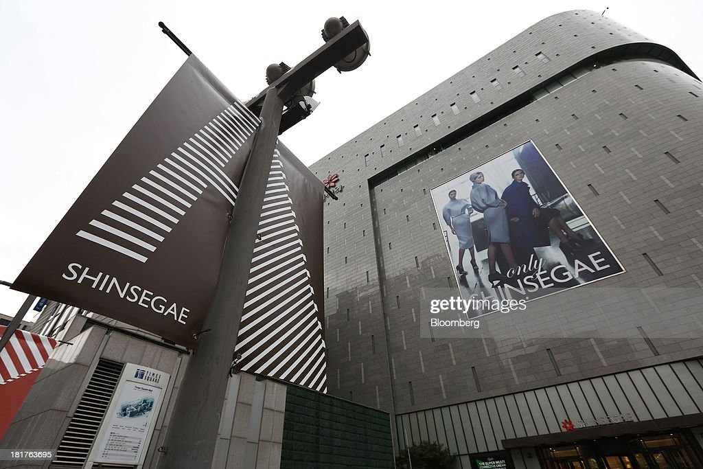 Shinsegae Co. signage is displayed outside one of the company's department stores in Seoul, South Korea, on Tuesday, Sept. 24, 2013. The South Korean economy faces headwinds, with record household debt and a sluggish housing market weighing on consumption. Photographer: SeongJoon Cho/Bloomberg via Getty Images