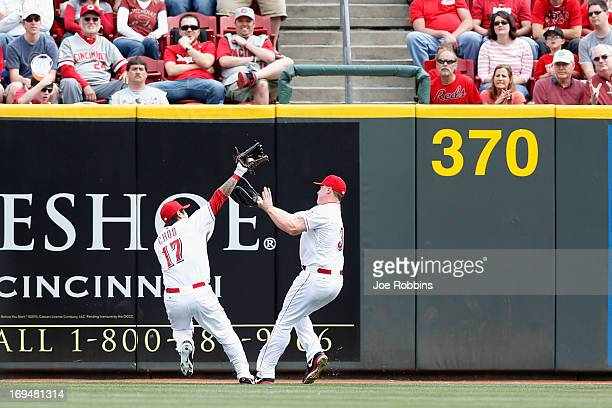 ShinSoo Choo and Jay Bruce of the Cincinnati Reds collide as Choo makes a catch near the center field wall against the Chicago Cubs during the game...