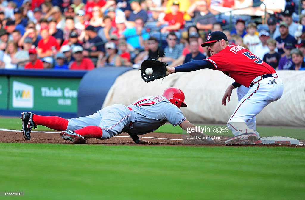 <a gi-track='captionPersonalityLinkClicked' href=/galleries/search?phrase=Shin-Soo+Choo&family=editorial&specificpeople=196543 ng-click='$event.stopPropagation()'>Shin-Soo Choo</a> #17 of the Cincinnati Reds dives back to first base against <a gi-track='captionPersonalityLinkClicked' href=/galleries/search?phrase=Freddie+Freeman&family=editorial&specificpeople=5743987 ng-click='$event.stopPropagation()'>Freddie Freeman</a> #5 of the Atlanta Braves at Turner Field on July 12, 2013 in Atlanta, Georgia.