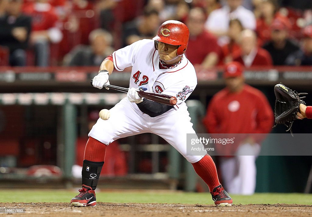 Shin-Soo Choo of the Cincinnati Reds hits a sacrifice bunt in the 8th inning during the game against the Philadelphia Phillies at Great American Ball Park on April 15, 2013 in Cincinnati, Ohio. All uniformed team members are wearing jersey number 42 in honor of Jackie Robinson Day.