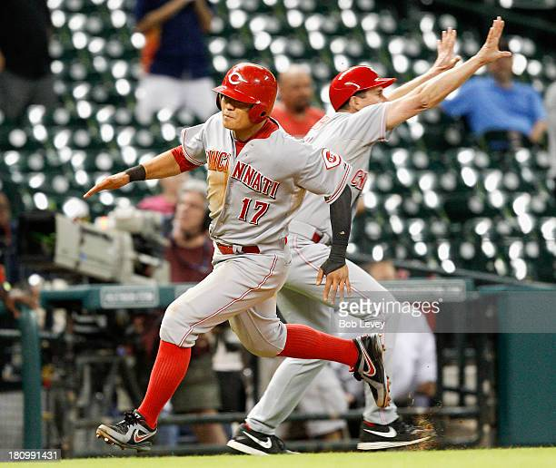 ShinSoo Choo of the Cincinnati Reds scores in the thirteenth inning on a double by Jay Bruce as third base coach Mark Berry holds up the runner...