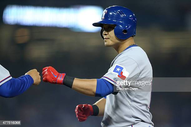 ShinSoo Choo of the Texas Rangers bumps fists with first base coach Hector Ortiz after hitting a single in the eighth inning against the Los Angeles...