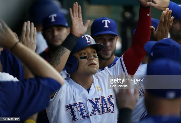 ShinSoo Choo of the Texas Rangers celebrates with teammates after scoring against the Los Angeles Angels of Anaheim during the first inning at Globe...