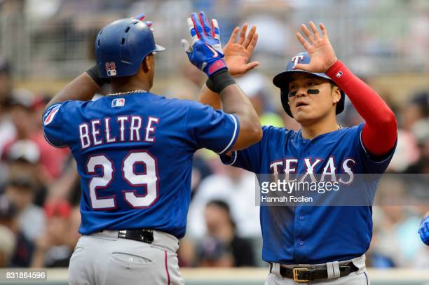 ShinSoo Choo of the Texas Rangers congratulates teammate Adrian Beltre on a home run against the Minnesota Twins during the game on August 6 2017 at...