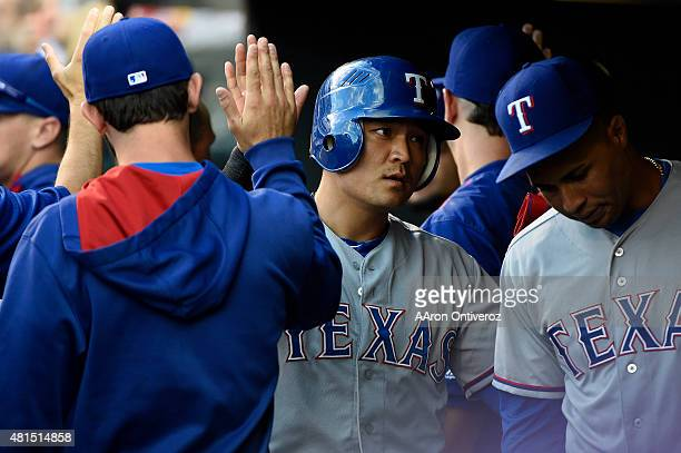ShinSoo Choo of the Texas Rangers high fives teammates after scoring with Robinson Chirinos to give the Rangers a 30 lead against the Colorado...