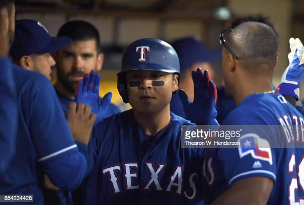 ShinSoo Choo of the Texas Rangers is congratulated by teammates after he hit a solo home run against the Oakland Athletics in the top of the third...
