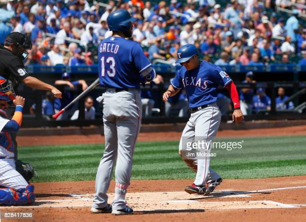 ShinSoo Choo of the Texas Rangers scores from third base on a balk in the first inning against the New York Mets as teammate Joey Gallo looks on at...