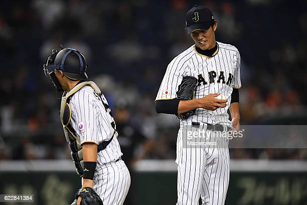 Shintaro Fujinami and Motohiro Shima of Japan speak in the seventh inning during the international friendly match between Japan and Netherlands at...