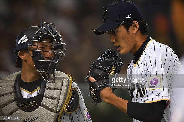 Shintaro Fujinami and Motohiro Shima of Japan speak in the sixth inning during the international friendly match between Japan and Netherlands at the...