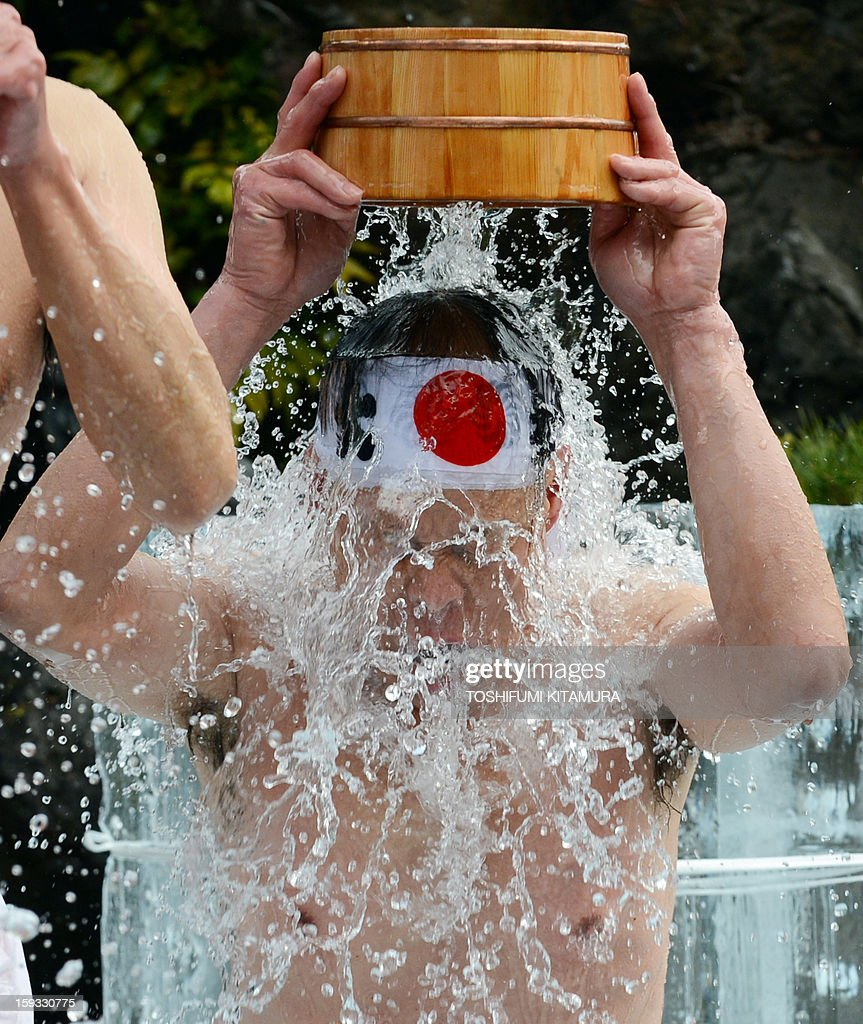 A Shinto believer pours cold water over himself to purify his body and soul as part of the new year endurance show at Kanda Shrine, known as Kanda Myojin, in Tokyo on January 12, 2013. About 50 people participated in the annual winter event. AFP PHOTO / TOSHIFUMI KITAMURA