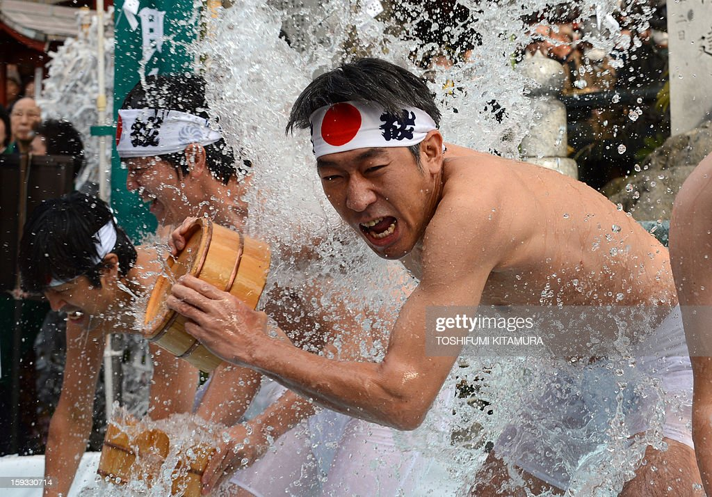 Shinto believers pour cold water over themselves to purify their bodies and souls as part of the new year endurance show at Kanda Shrine, known as Kanda Myojin, in Tokyo on January 12, 2013. About 50 people participated in the annual winter event. AFP PHOTO / TOSHIFUMI KITAMURA
