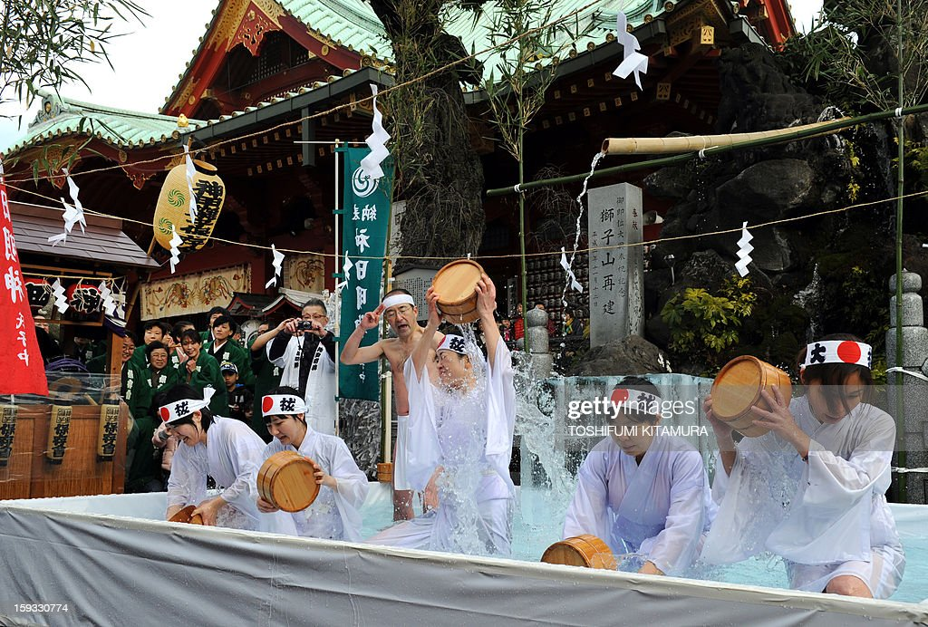 Shinto believers pour cold water over themselves to purify their bodies and souls as part of the new year endurance show at Kanda Shrine, known as Kanda Myojin, in Tokyo on January 12, 2013. About 50 people participated in the annual winter event.