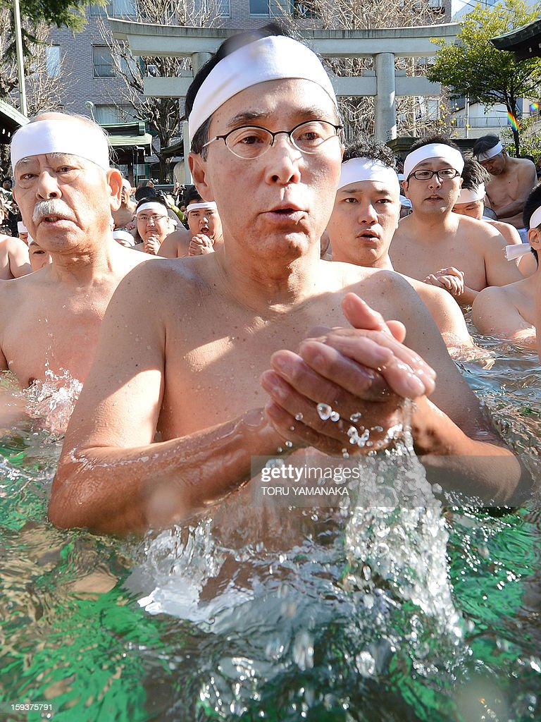 Shinto believers pray in a ice-pool to purify their bodies and souls as they display their endurance skills during a New Year's purification ceremony at Teppozu Irani Shrine in Tokyo on January 13, 2013. Some 100 believers attended the annual New Year ceremony in the cold winter air. AFP PHOTO / Toru YAMANAKA