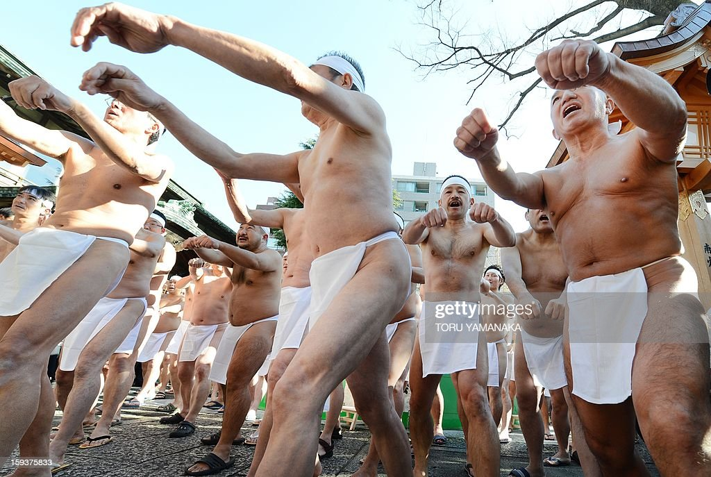 Shinto believers warm up before entering an ice-pool to pray to purify their bodies and souls as they display their endurance skills during a New Year's purification ceremony at Teppozu Irani Shrine in Tokyo on January 13, 2013. Some 100 believers attended the annual New Year ceremony in the cold winter air. AFP PHOTO / Toru YAMANAKA