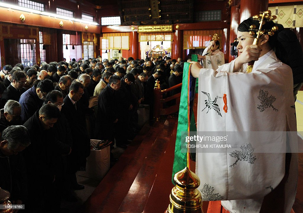 Shinto maidens (R) shake bells to 'purify' businessmen during a ceremony to pray for a good business year at the Kanda shrine in Tokyo on January 4, 2013, on the first business day after the new year holidays. Tokyo stocks jumped more than three percent on January 4, the first day of 2013 trading, following global rallies on a US deal to avert a 'fiscal cliff' of tax hikes and huge spending cuts.
