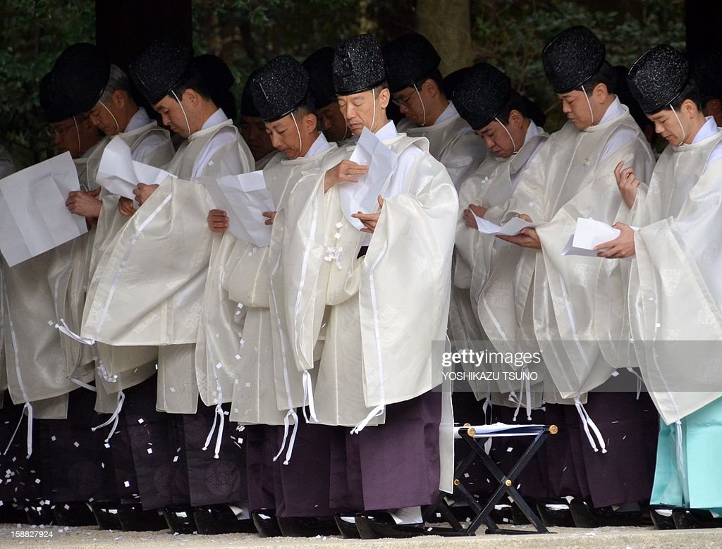 Shinto priests purify themselves with small piece of papers during a ritual end-of-the-year purification ceremony to prepare for New Year's Day at Meiji Shrine in Tokyo on December 31, 2012. Millions of Japanese people will visit shrines and temples across the country to celebrate New Year's Day, one of the most important holiday periods of the year here. AFP PHOTO / Yoshikazu TSUNO